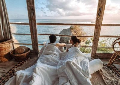 couple on a deck under a blanket looking out at the ocean